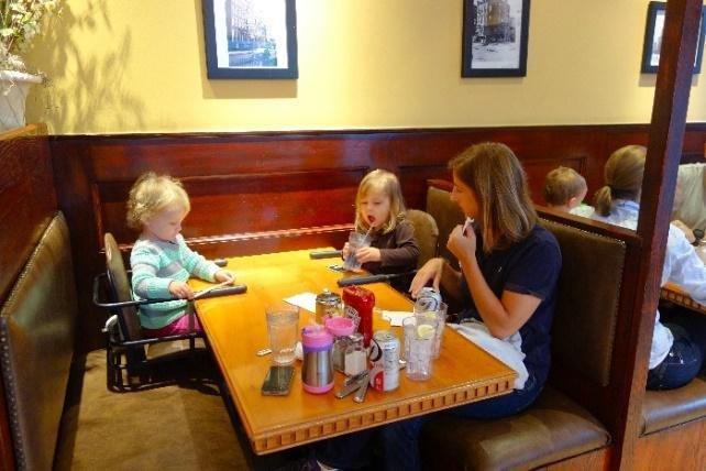 Kėdutės, padedančios šeimai pavalgyti kartu, pasiekti vaikui per aukštą stalą restorane pavyzdys.
