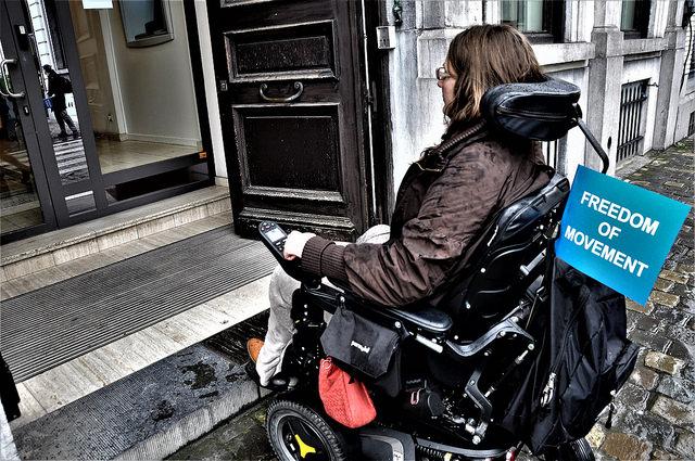 Asmuo neįgaliojo vežimėlyje prie įėjimo laiptų, Briuselis (Belgija)